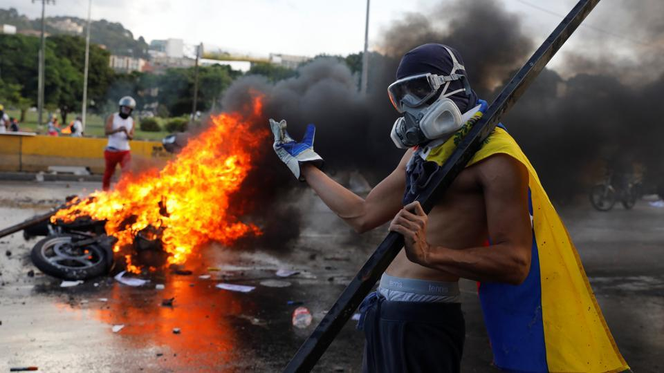An opposition supporter stands next to a burning riot security force motorcycle during clashes at a rally against Venezuelan President Nicolas Maduro's government in Caracas, Venezuela on June 22, 2017.  (Carlos Garcia Rawlins/REUTERS)