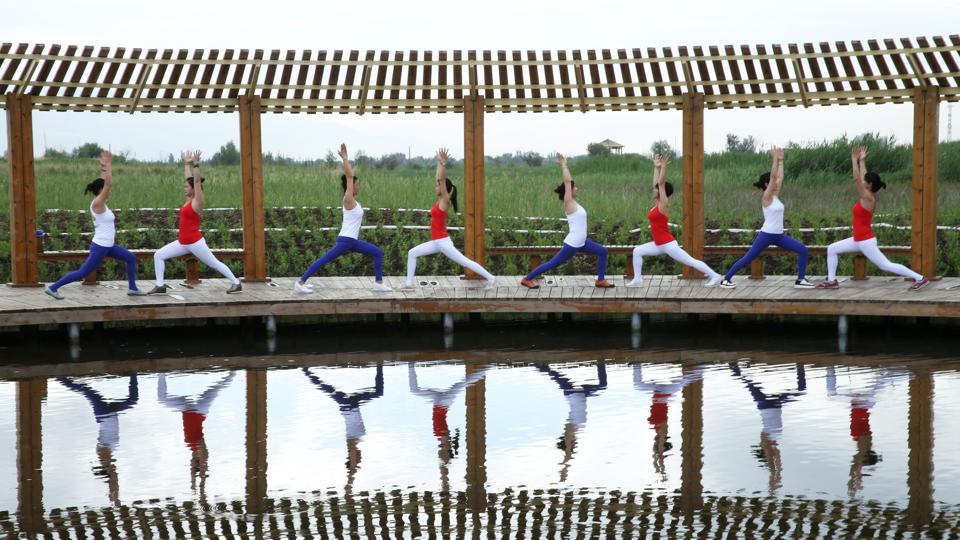 Yoga enthusiasts practice yoga at a wetland park on International Yoga Day, in Zhangye, China on June 21, 2017.  (REUTERS)