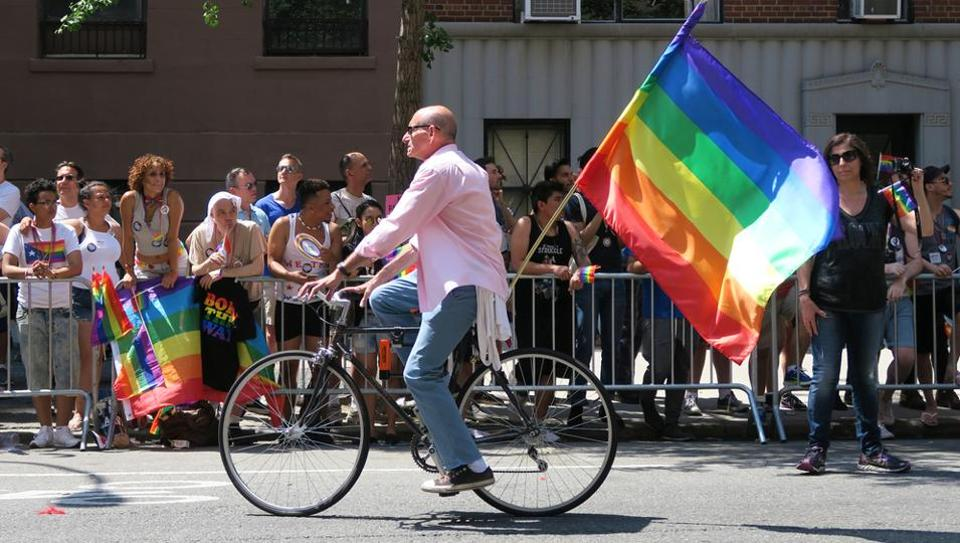 Man on a bicycle at the Gay Pride Parade on 5th ave, New York. The rainbow colours are the symbol of lesbian, gay, bisexual and transgender pride and diversity.