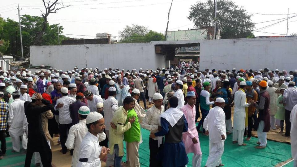 People gather at a mosque in Chhatarpur, MP, wearing black bands.