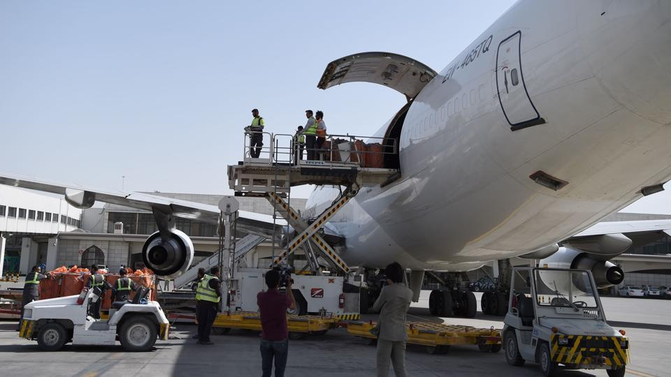 Afghan airport workers load the first cargo plane bound for India after the opening of the first Afghan-India air corridor ceremony in Kabul on June 19, 2017.