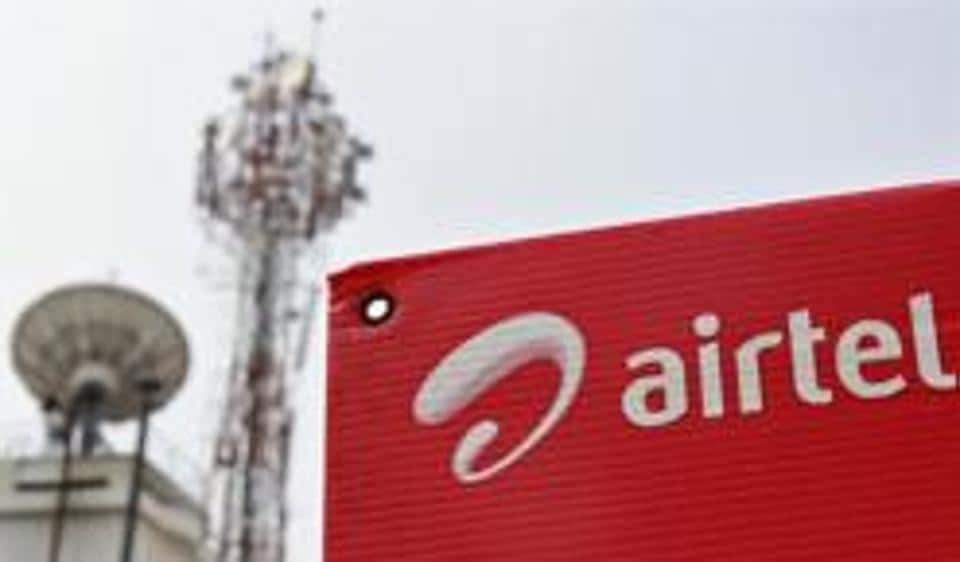 A Bharti Airtel advertisement board is installed against the backdrop of company's telecommunication tower.