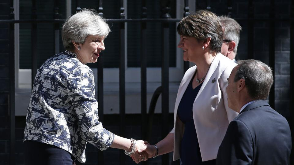 Britain's Prime Minister Theresa May (L) shakes hands with Democratic Unionist Party (DUP) leader Arlene Foster (C) as they arrive for a meeting at 10 Downing Street in central London on Monday.
