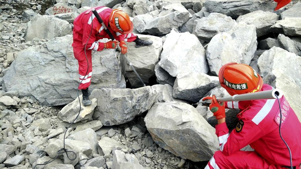 Paramilitary rescuers use sensors to check for signs of life in the rubble at the site of a landslide. According to official Xinhua News Agency rescue crews were ordered on Monday to evacuate the site of a deadly landslide in southwestern China over concerns of a second landslide.  (AP)