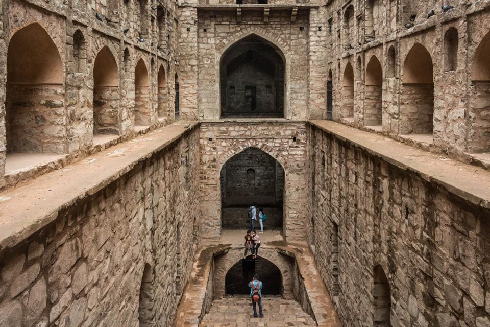 A frontal view of the 'Agrasen ki Baoli' with tourists posing for pictures. This baoli is a monument protected by the Archaeological Survey of India (ASI) and is a 60-meter long and 15-meter wide historical step well on near Connaught Place in New Delhi.