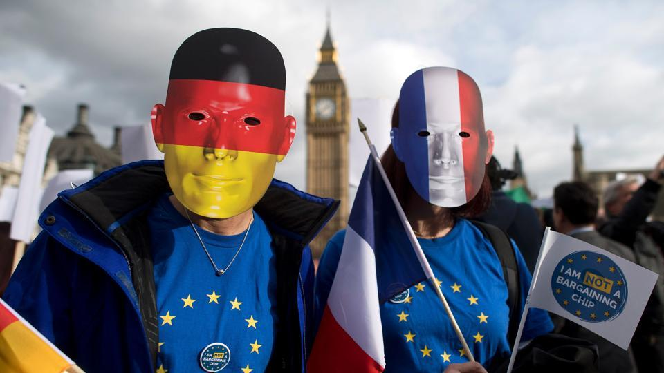 Protesters wearing German and French flags on their masks during a demonstration in London in February as part of a national day of action in support of migrants in the UK.