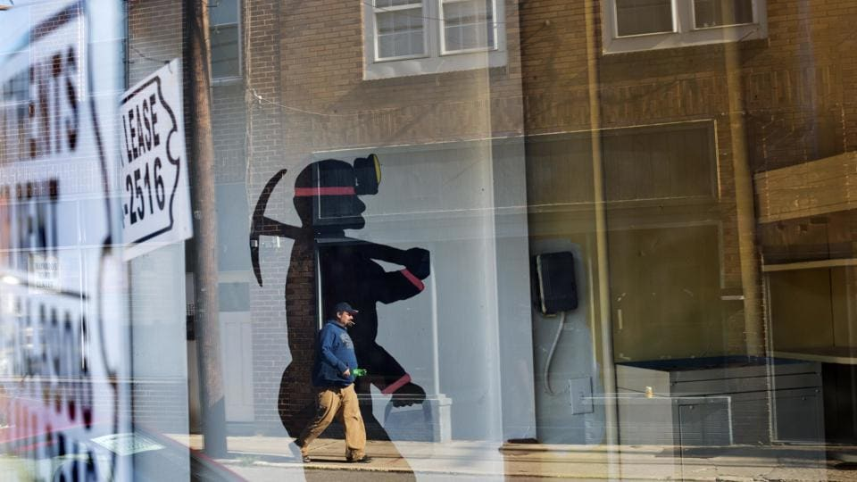 A mural of a coal miner stands in an empty storefront as signs advertising vacant apartments and stores hang in the windows along the main business street in Cumberland in the United States. Reducing coal emissions was a critical piece of the 2015 Paris climate accord that Trump announced this month he wants to exit. (David Goldman/AP)