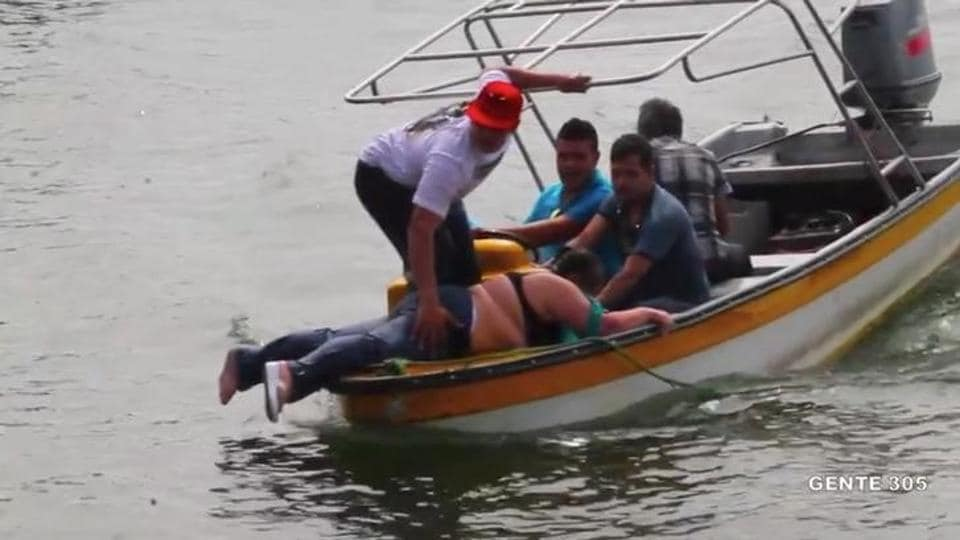People on a boat rescue passengers of a sinking tourist ferry (not pictured) in the Guatape reservoir in Colombia June 25, 2017 in this still image taken from video obtained from social media.
