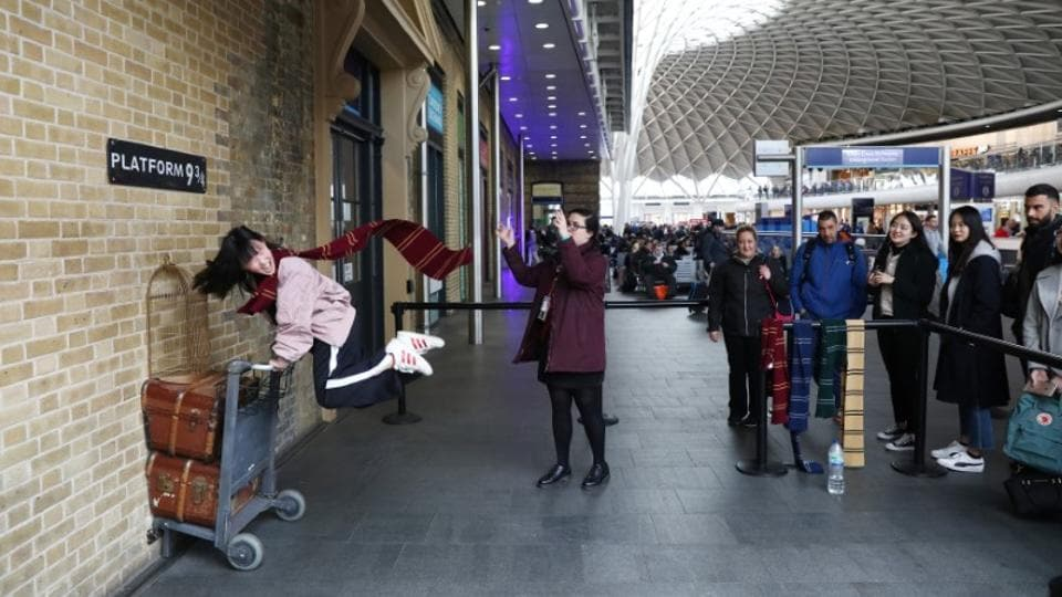 A Harry Potter fan poses for a photograph during a visit to Platform Nine and Three-Quarters at Kings Cross station in London. (Neil Hall/Reuters)