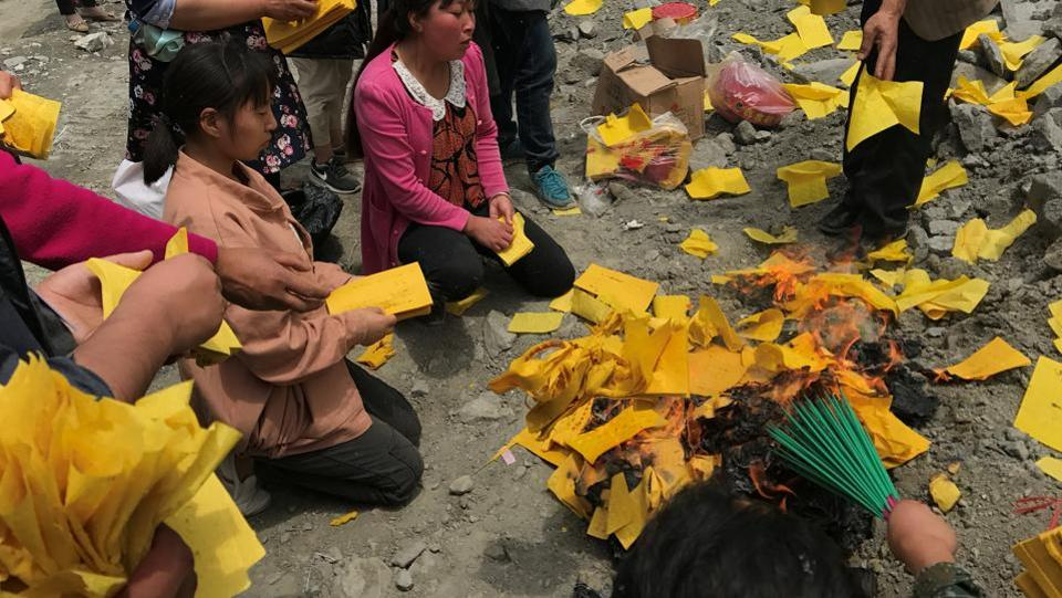 Relatives of victims burn incense and paper money to mourn their dead relatives at the site of a landslide in Sichuan Province.  (REUTERS)