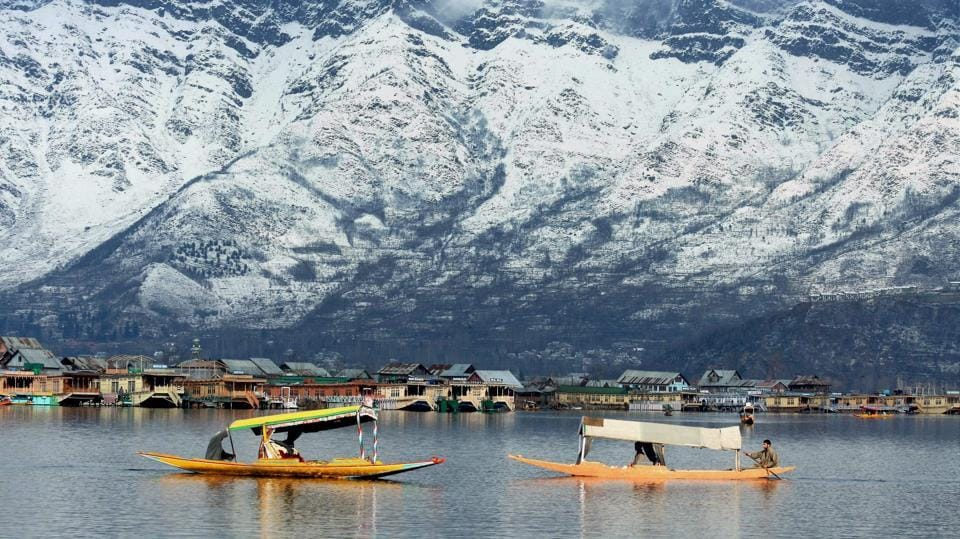 Shikaras float along the Dal lake against the backdrop of snow-covered Zabarwan hills in Srinagar.