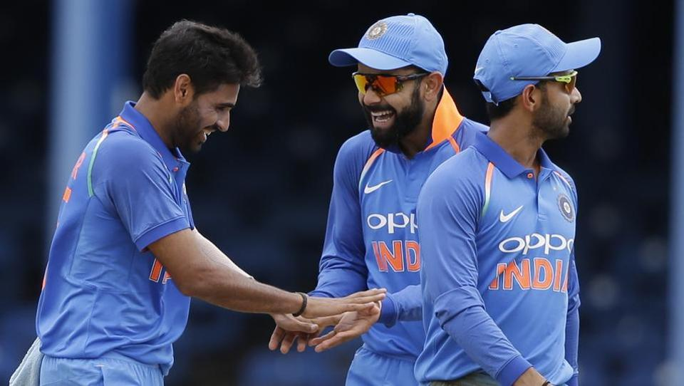 Bhuvneshwar Kumar (left) celebrates with India captain Virat Kohli after the dismissal of West Indies' Jason Mohammed during the second ODI cricket match at Queen's Park Oval in Port of Spain. Get full cricket score of India vs West Indies 2nd ODI here