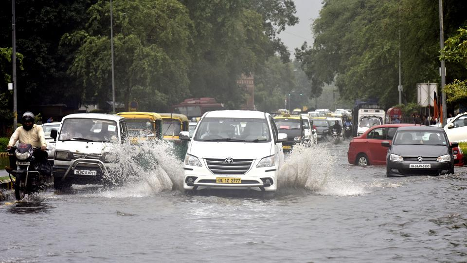 Vehicles pass through a water-logged street at Baba Kharak Singh Marg in New Delhi on  June 21.