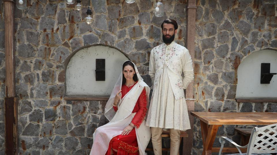 Model Arnela Zekovic in a white tussar silk sari  by Nicobar, draped over a red ruffled dress by Mint Blush; Model Vishwaraj Singh Lavera in a circular kurta teamed with churidaar and floral Nehru jacket(HT Photo/ Shara Ashraf)  (HT Photo/ Shara Ashraf; Styling: Shara Ashraf and Akshay Kaushal)