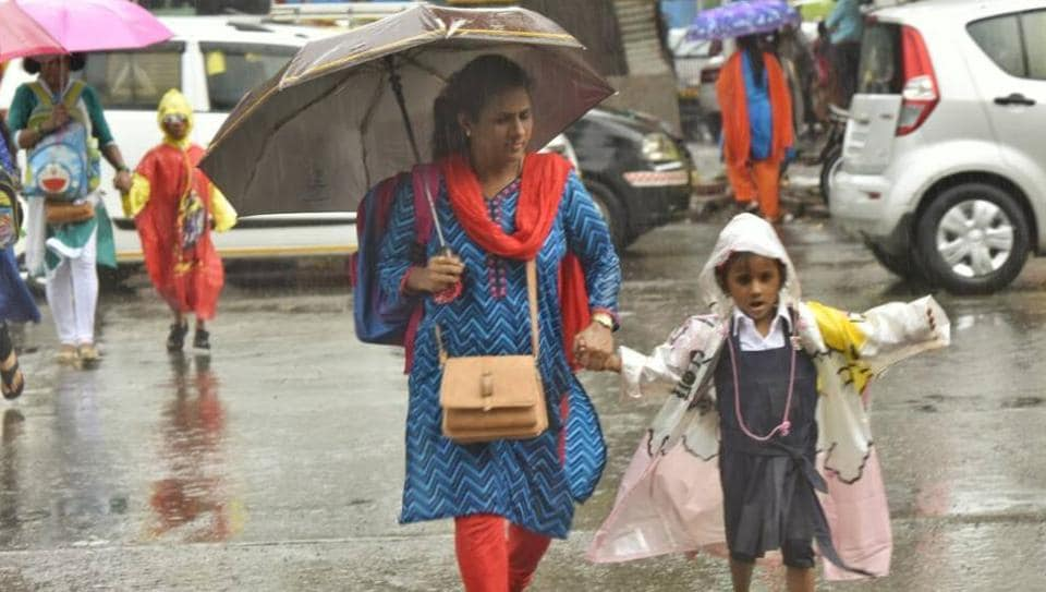 People had to wade through waterlogged streets across Mumbai. (In pic) A child with her mother at Shivaji Park, Dadar.