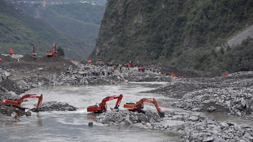 Rescue workers are seen at the site of a landslide in Xinmo village, Diexi town of Maoxian county, Sichuan province.