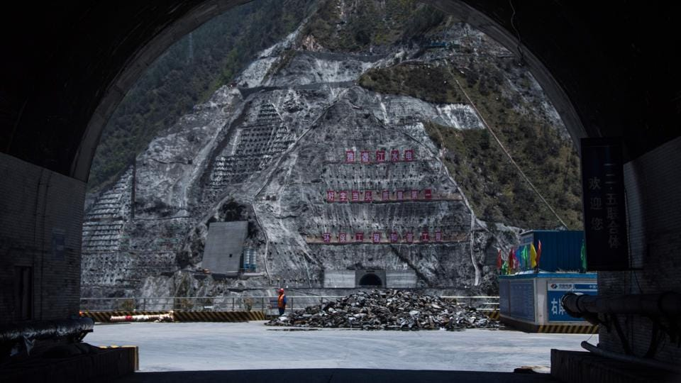 A worker stands next to the construction site of the Lianghekou dam. China had just two dams till 1949 but now has nearly half of the world's  total  number of dams. (AFP)