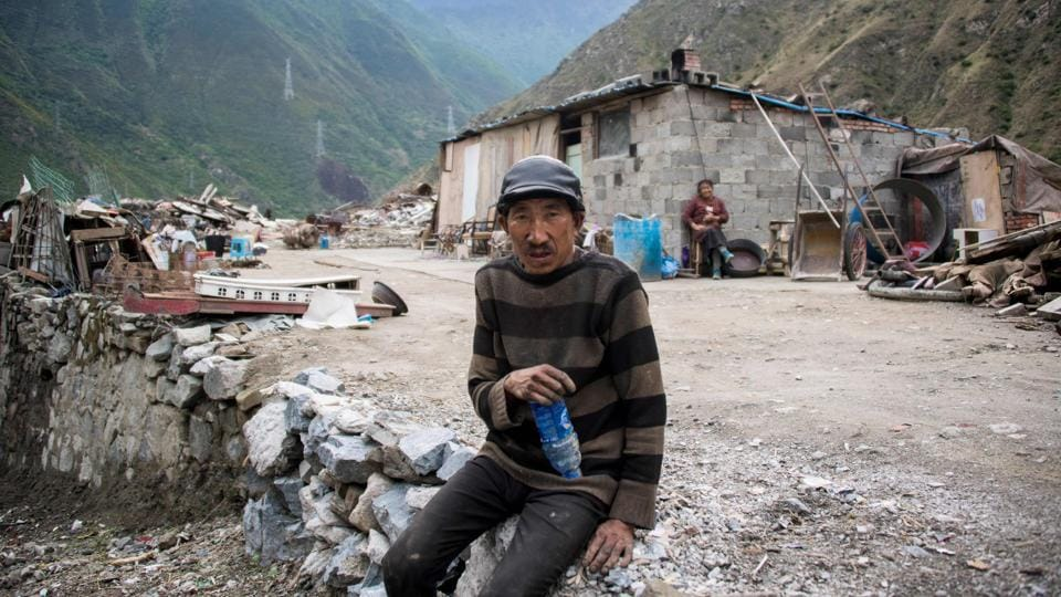 A man sits next to the debris of demolished houses and a makeshift hut  near Lianghekou. Beijing is scaling up hydropower at breakneck pace as part of an ambitious undertaking to reduce the country's dependence on coal and cut emissions that have made it the world's top polluter.  (AFP)