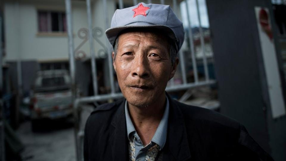 Yang Renyi who is seeking compensation money for his old house poses for a portrait in front of his new house near Lianghekou. Beginning in the 1990s, more than a million were moved for the Three Gorges Dam, the world's largest in terms of capacity with thousands still mired in poverty.  (AFP)