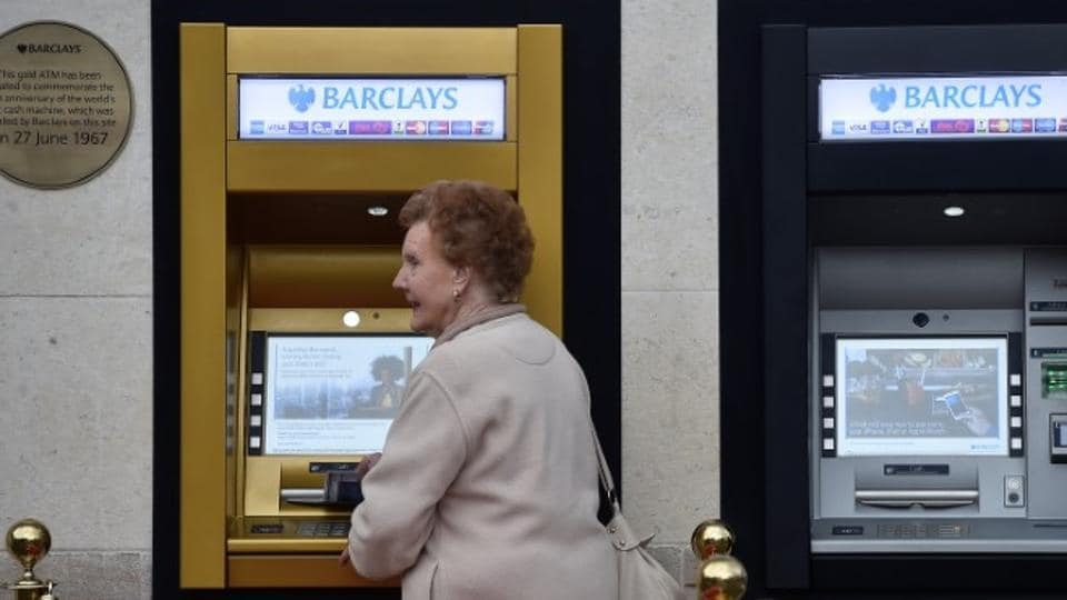 A woman uses the golden ATM, marking the location of the first 'hole in the wall,' which opened fifty years ago, in Enfield, Britain.