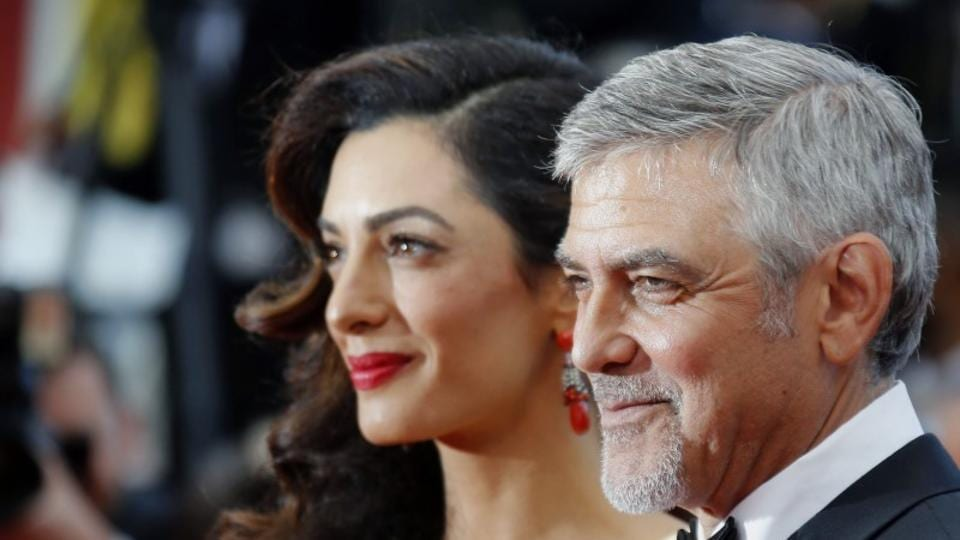 George Clooney and his wife Amal pose on the red carpet for the screening of the film Money Monster.