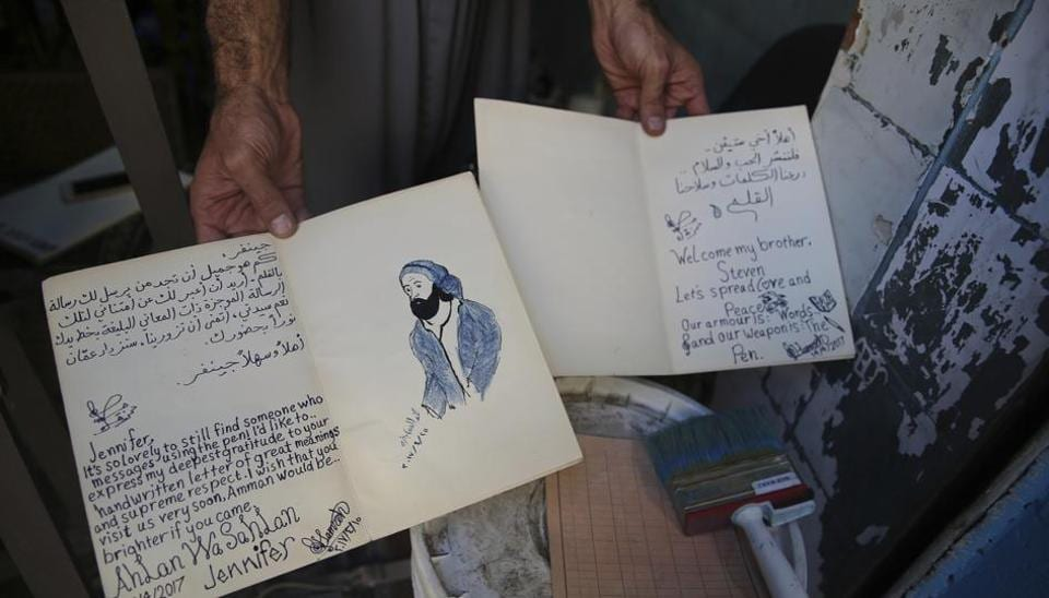 Hamzeh AlMaaytah shows two of many letters he handwrites himself in response to text or Facebook messages, at his Mahall al-Maa bookstore, in Jordan's capital, Amman.