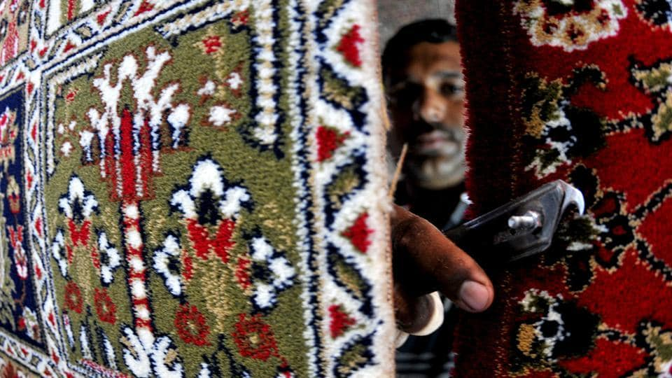 A employee works at a carpet weaving machine at a factory in Bari Brahmana Industrial area. The famed 'Kashmiri' carpet is known for its traditionally high thread count and the number of knots, often ranging in the thousands. This allows the weaver to bring out highly detailed designs in the rugs.  (Nitin Kanotra/HT Photo)
