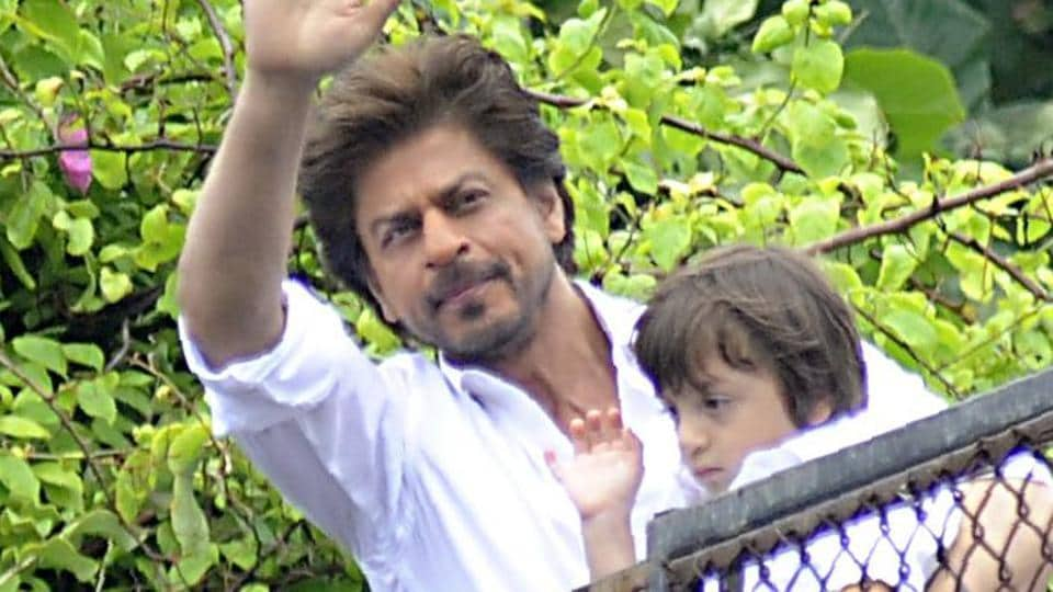 Shah Rukh Khan holds his son Abram Khan as he waves to fans outside his home at the start of Eid al-Fitr in Mumbai on June 26, 2017. /