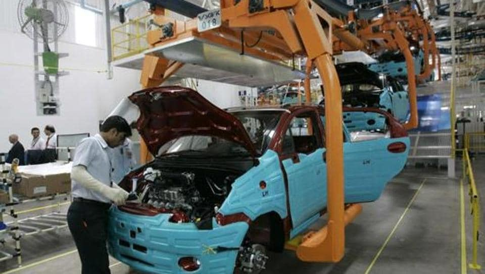 A worker assembles a new vehicle on the assembly line at the General Motors Corp. in Talegaon, near Mumbai.