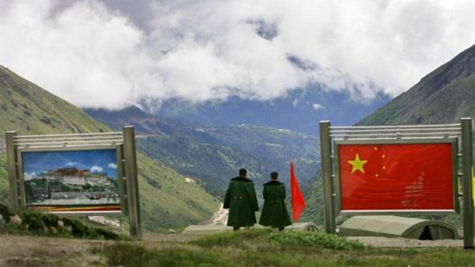 Chinese army officers oversee preparations as they stand between pictures of the Patola Palace, left, and the Chinese flag, on the Chinese side of the international border at Nathula Pass, in Sikkim.