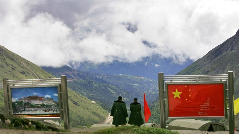 Chinese army officers oversee preparations as they stand between pictures of the Patola Palace, left, and the Chinese flag, on the Chinese side of the international border at Nathula Pass, in northeastern Indian state of Sikkim.