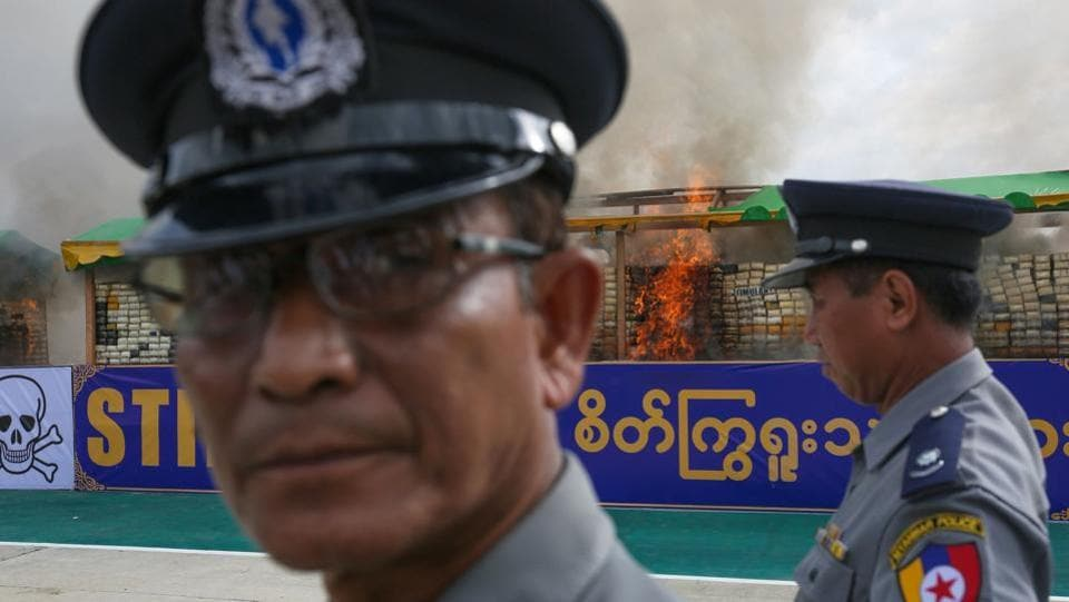 Myanmar police stand near the site where confiscated drugs were burnt to commemorate World Anti-Drugs Day on the outskirts of Yangon.  According to a senior police official this was the biggest burning of seized drugs in the history of Myanmar.  (AFP)