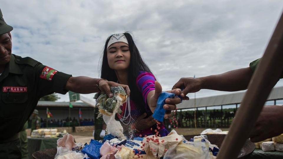 An ethnic Wa woman from UWSA (United Wa State Army) empties a packet  of Ya Ba drug before they are set on fire during a drug burning ceremony.  (AFP)