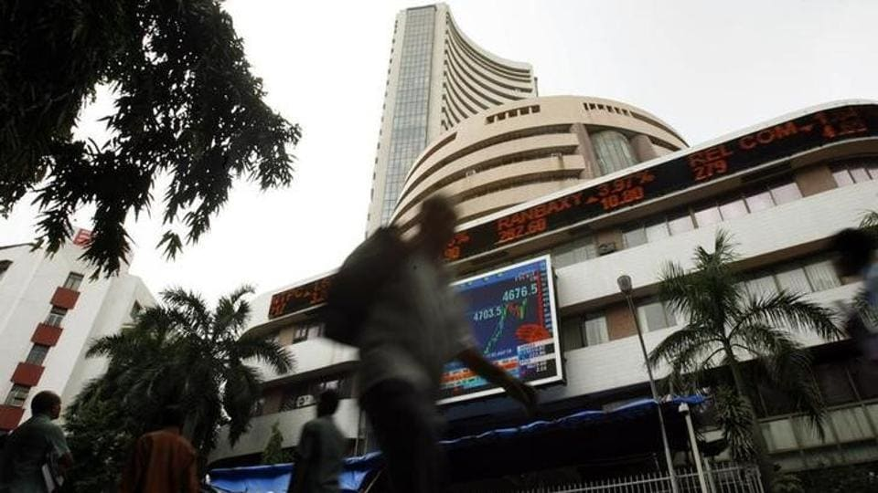 People walk pass the Bombay Stock Exchange (BSE) building displaying India's benchmark share index on its facade.