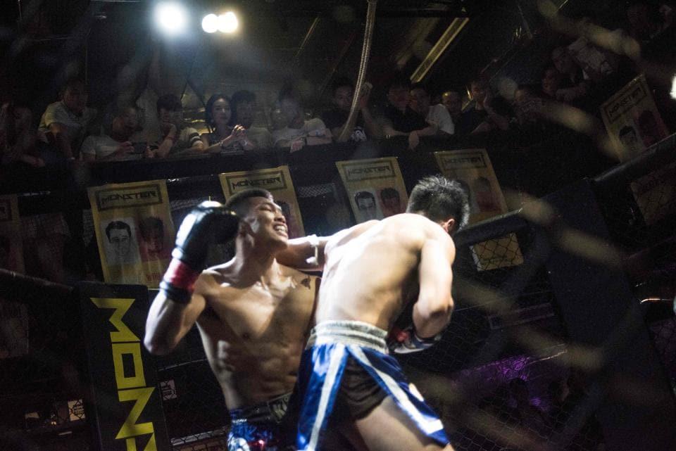 Two men fighting in the dimly lit Monster Club in Chengdu.