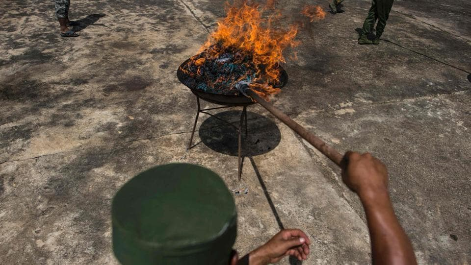 A member of UWSA  sets a pile of seized drugs on fire during a drug burning ceremony. The huge seizures are often touted by Myanmar and Thailand as proof that they are making inroads into the vast regional drug trade.  (AFP)