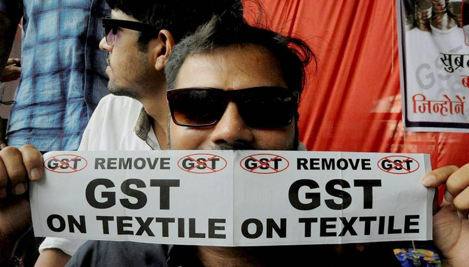 A man holds a poster with an anti-GST message printed on it during a sit-in by traders protesting the soon-to-be-implemented tax regime, in Surat.