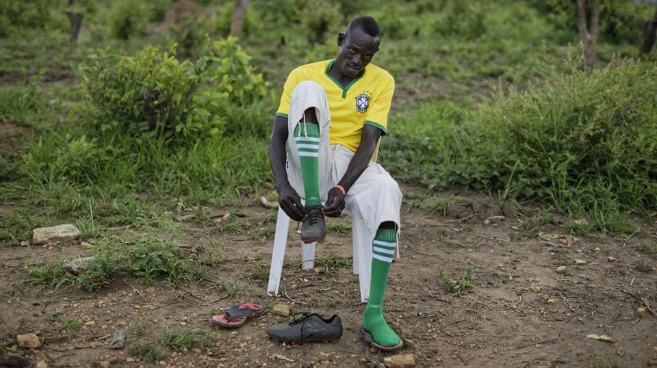 A South Sudanese refugee soccer player laces his boots as he prepares for a match. (Ben Curtis / AP)