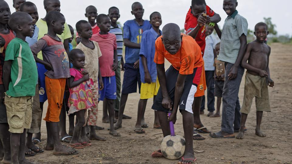 A refugee boy pumps up an old soccer ball, in the Bidi Bidi refugee settlement in northern Uganda.  (Ben Curtis / AP)