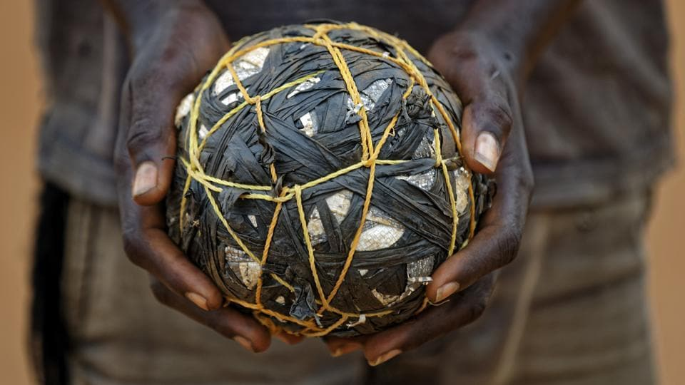 A South Sudanese refugee boy holds a makeshift ball as he plays with his friends.  (Ben Curtis / AP)