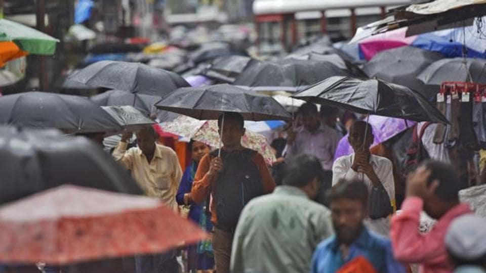 People shield themselves under umbrellas at Bhandup.