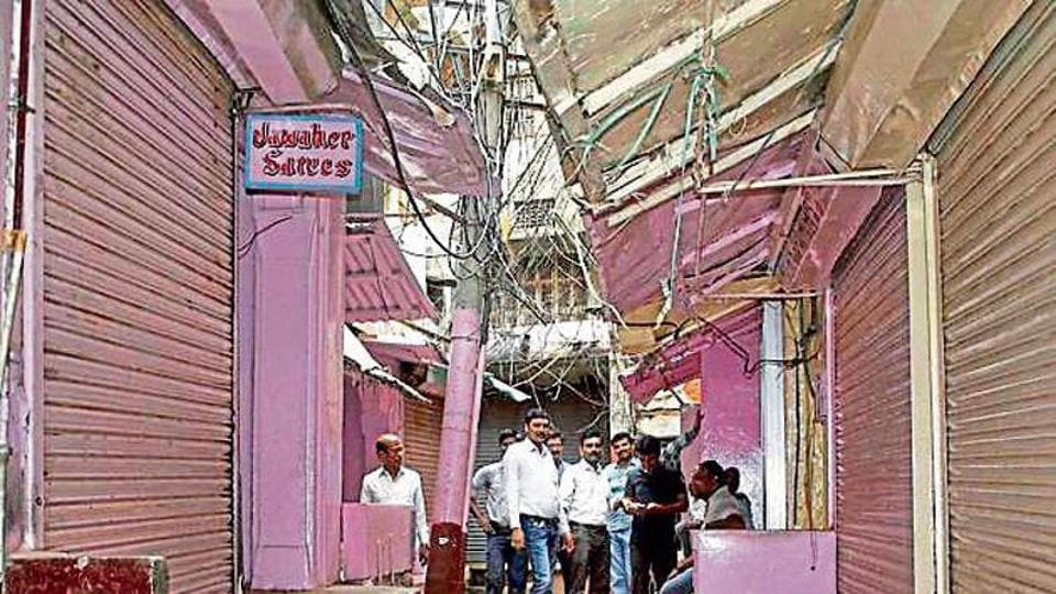 Shopkeepers sit around in the closed Banarasi Saree Bazar during a bandh called against GST in Varanasi on Wednesday.