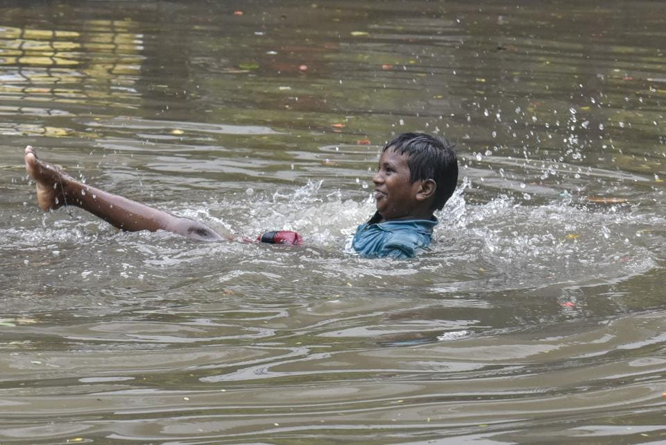 A child plays on a flooded street in Sion on Tuesday.