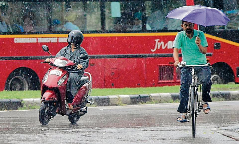 Commuters brave the rain in Chandigarh on Wednesday. The temperature was 9°C below normal for this time of the year.