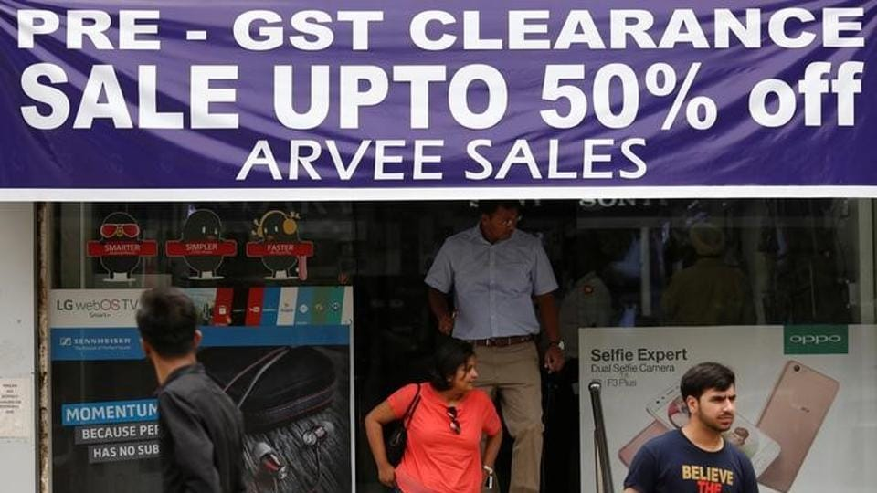 A banner promotes Goods and Services Tax (GST) clearance sale as customers walk out of an electronic shop at a market in New Delhi.