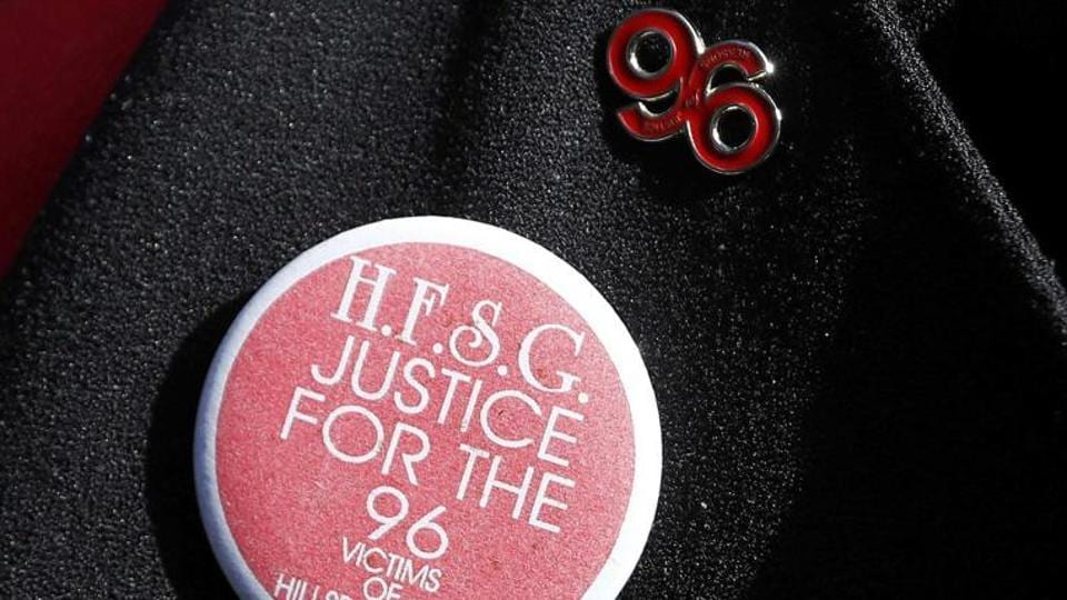 A relative wears lapel badges as they arrive to hear the jury deliver its verdict on the Hillsborough disaster.