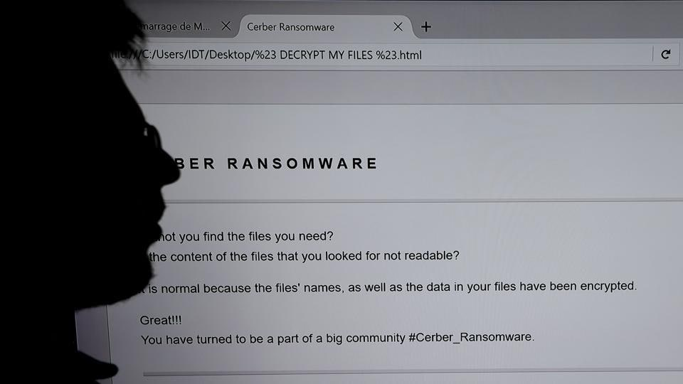 This file photograph shows an IT researcher as he stands next to a giant screen of a computer infected by a ransomware at the LHS (High Security Laboratory) of the INRIA (National Institute for Research in Computer Science and Automation) in Rennes. Several multinational companies said June 27, 2017, that they had been targeted in an international cyberattack which started in Russia and Ukraine before spreading to western Europe.