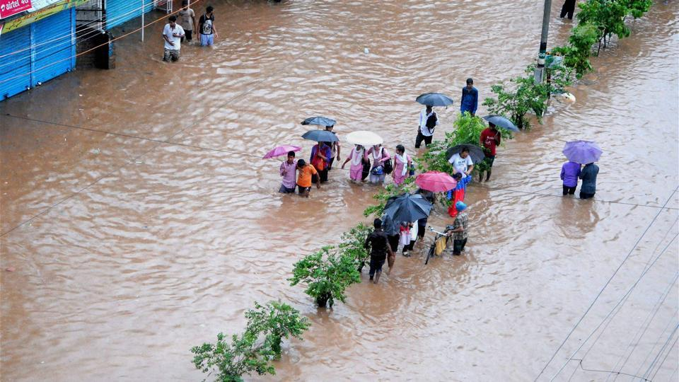 People make their way through a flooded street after heavy rainfall in Guwahati, Assam.