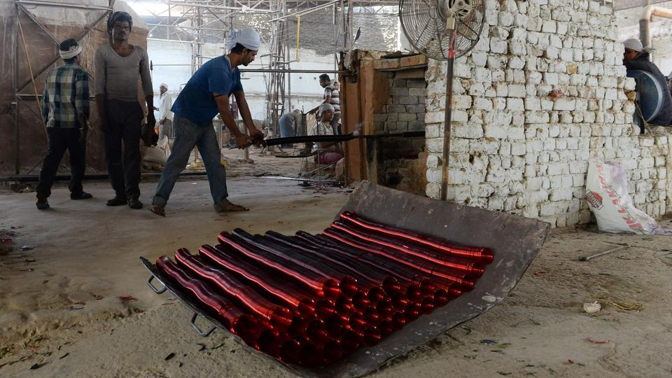 These factories date back to almost as far as the Mughal-era mausoleum. A Supreme Court ruling in 1999, giving Firozabad two years to retrofit their factories with gas instead of coal, has gradually eroded their razor-thin margins, pushing many to the wall. (Sajjad Hussain /AFP)