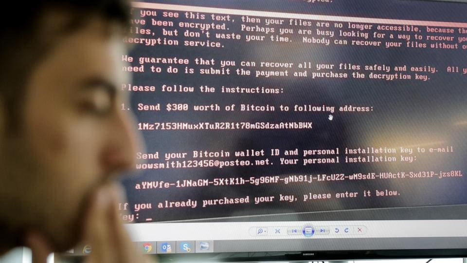 Razvan Muresan, a Bitdefender public relations specialist is backdropped by a screenshot of the message displayed on computers affected by the latest cyberattack, in Bucharest, Romania, on June 28.